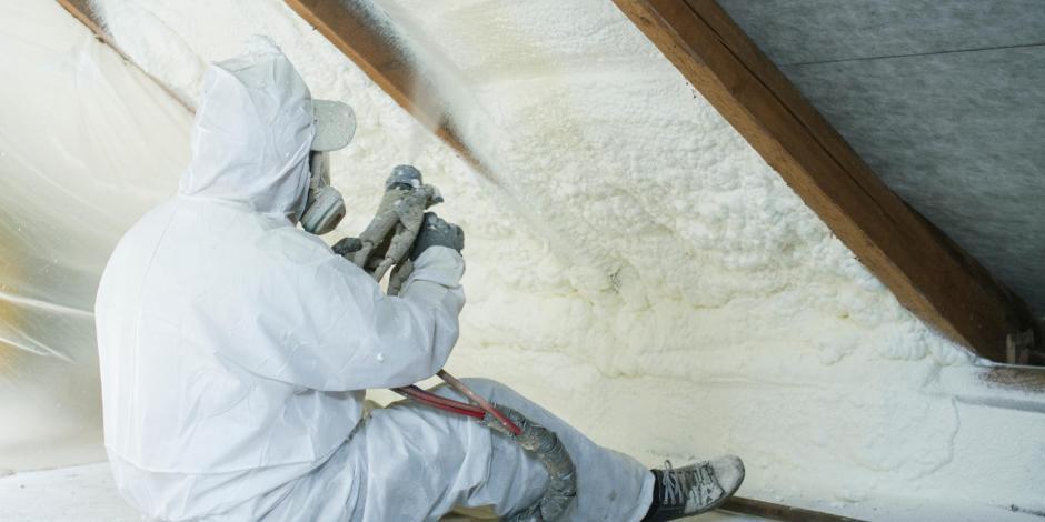 Worker applying spray foam insulation in attic