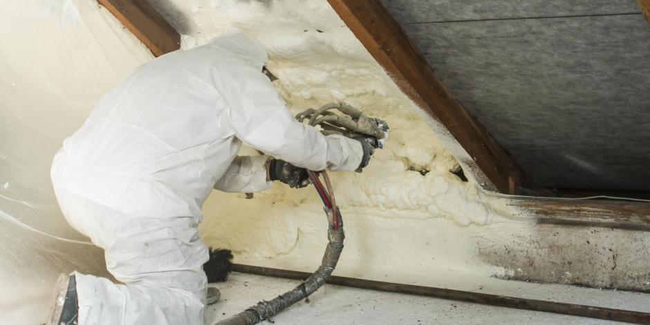 Worker applying spray foam in commercial building