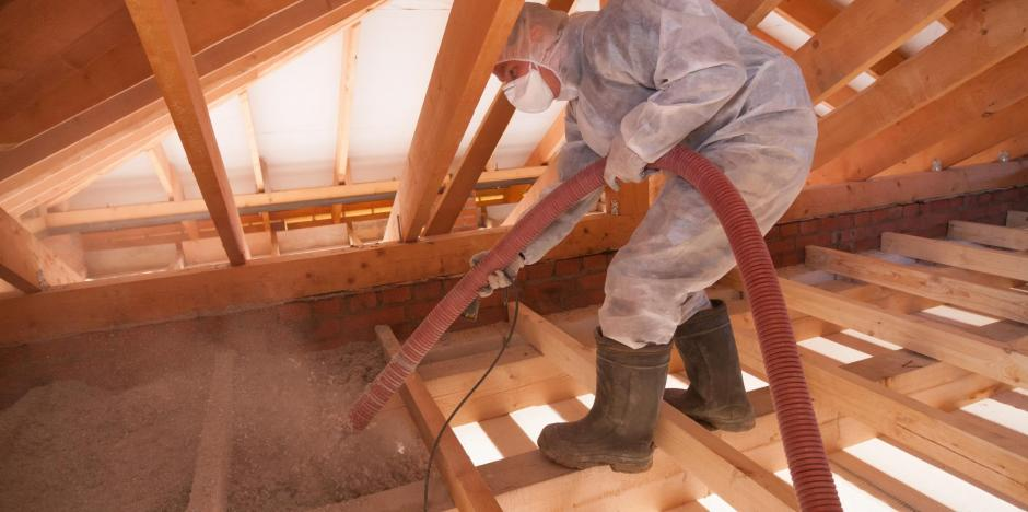 Worker blowing cellulose insulation in attic