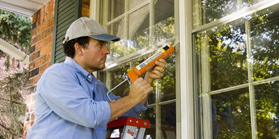 Worker applying caulk to windows