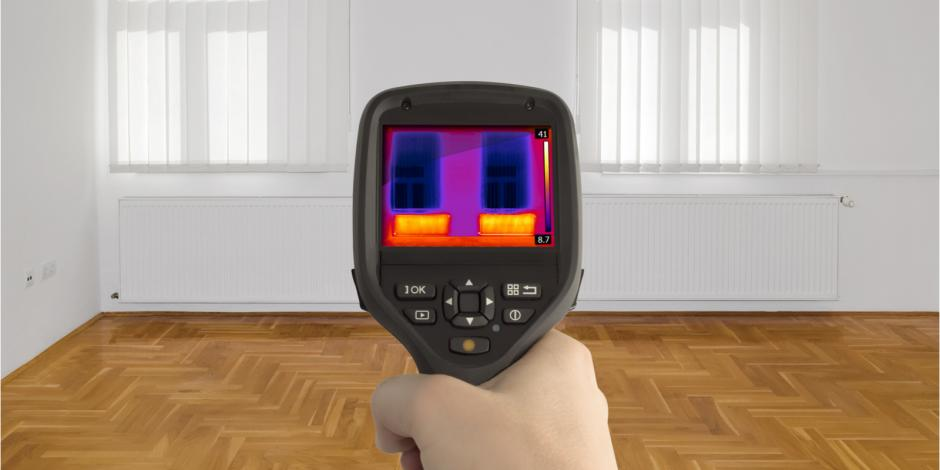 Hand holding infrared camera up in room