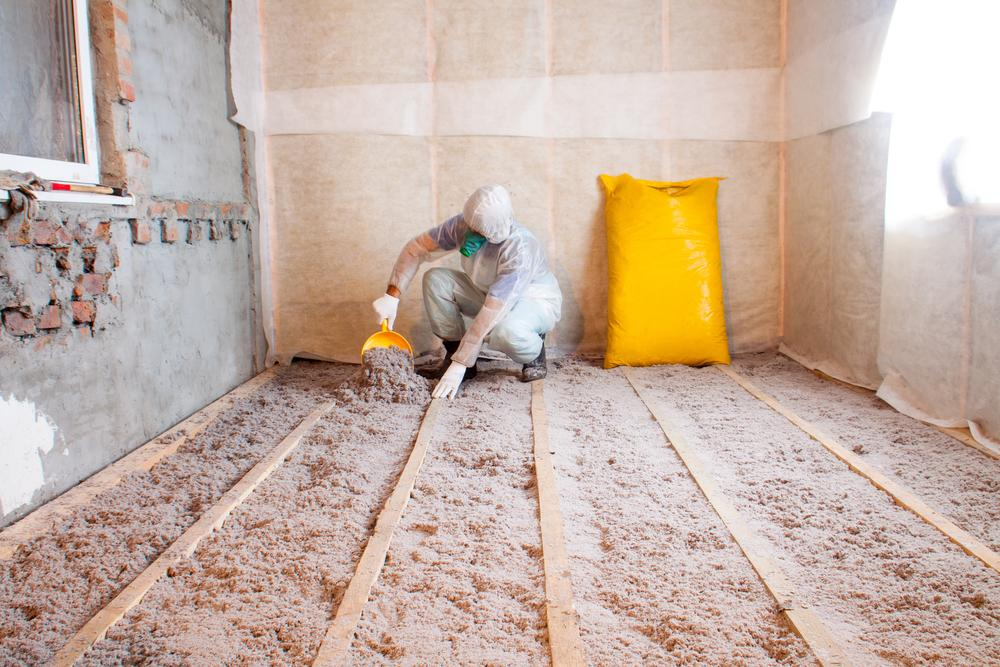Worker applying cellulose insulation in attic floor